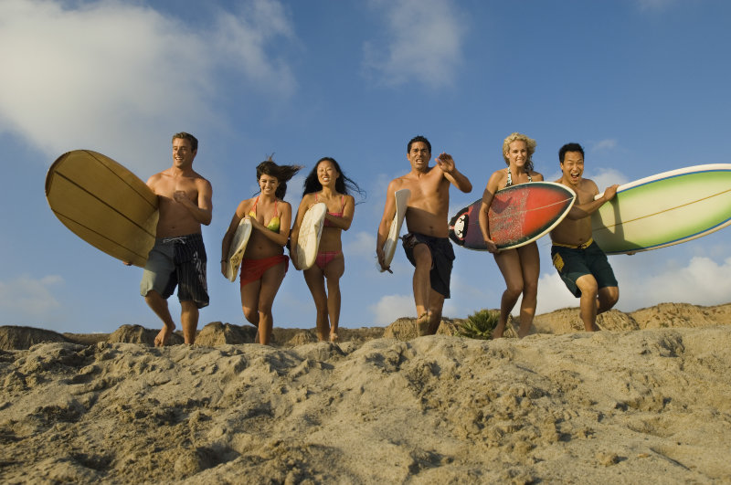 Friends With Surfboards Running On Sandy Beach
